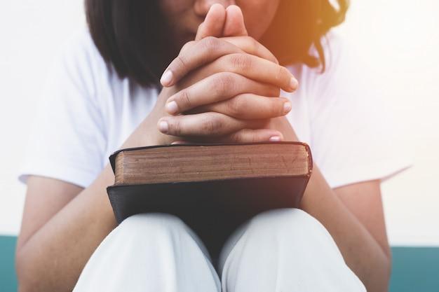 Jovem mulher orando com a bíblia sagrada