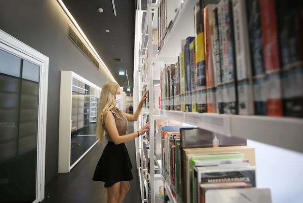 Jovem mulher ou garota de pé na livraria ou biblioteca e procure no livro.