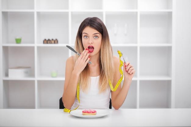Jovem mulher ou menina adolescente segurando o prato com como símbolo de comida da dieta louca em distúrbio nutricional