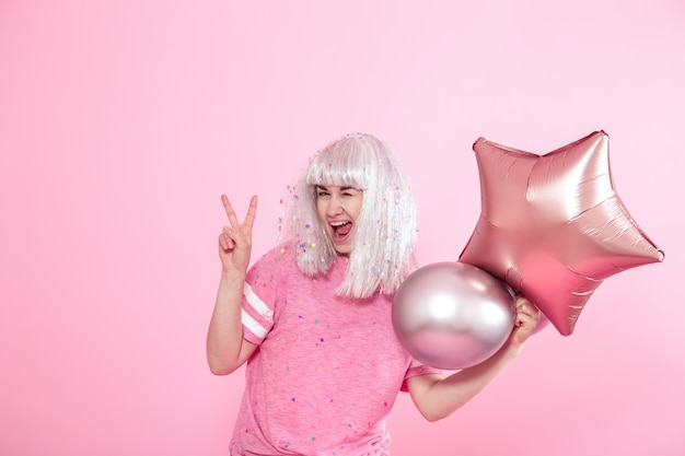 Jovem mulher ou menina com balões e mostra dois dedos. paz. conceito de férias e festa.