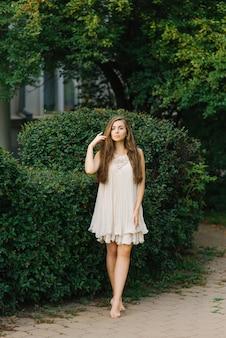 Jovem mulher ou menina em um vestido leve voa com os pés descalços através de um parque da cidade no verão