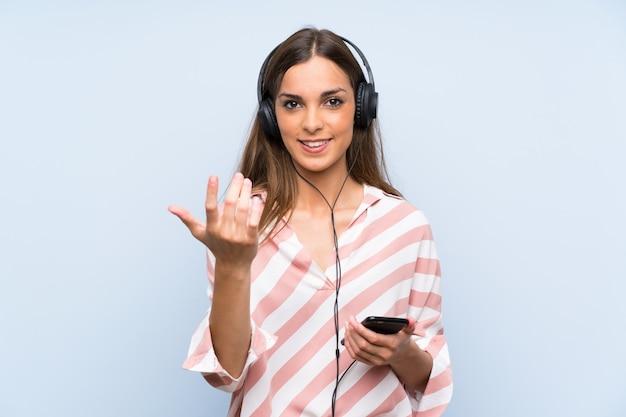Jovem mulher ouvindo música com um celular, convidando para vir com a mão