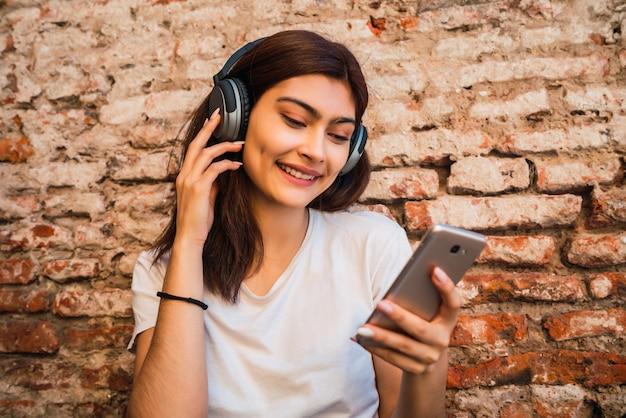 Jovem mulher ouvindo música e usando o smartphone.