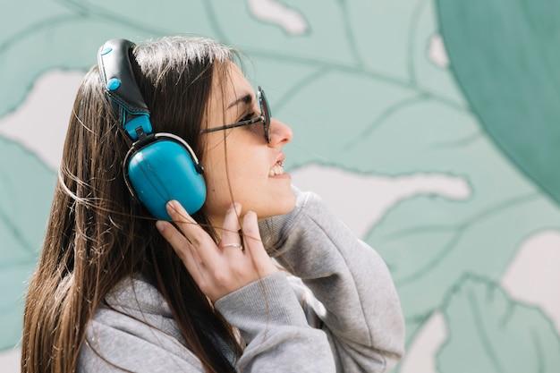 Jovem mulher ouvindo música em fones de ouvido azuis