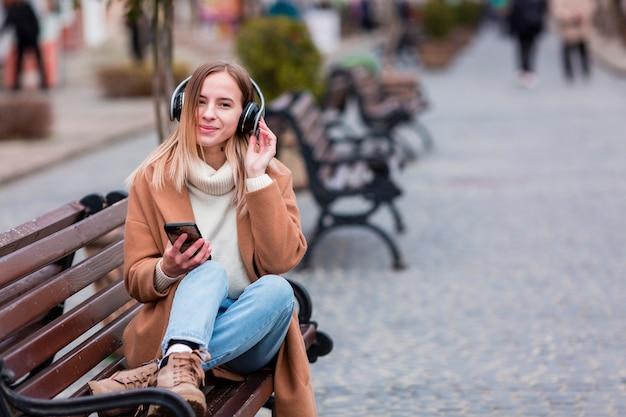 Jovem mulher ouvindo música em fones de ouvido com espaço de cópia