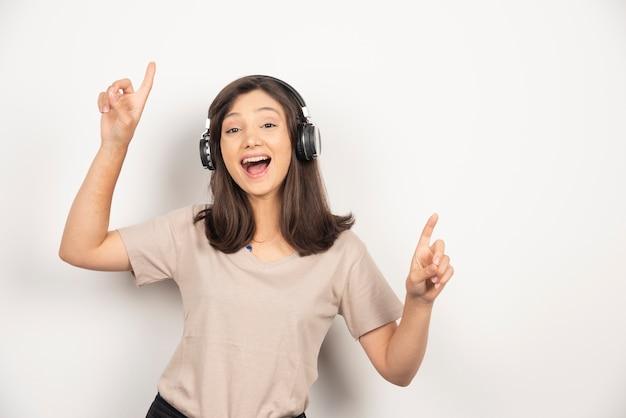 Jovem mulher ouvindo música em fones de ouvido e dançando.