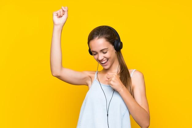 Jovem mulher ouvindo música isolada na parede amarela, celebrando uma vitória