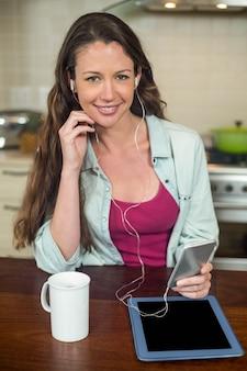 Jovem mulher ouvindo música no smartphone com tablet e caneca de café na bancada da cozinha