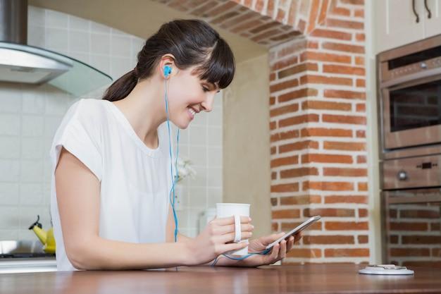Jovem mulher ouvindo música no smartphone enquanto tomando café na cozinha