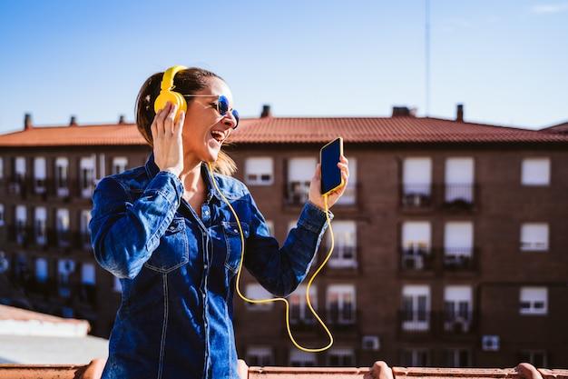 Jovem mulher ouvindo música no telefone celular e fone de ouvido amarelo. diversão e estilo de vida