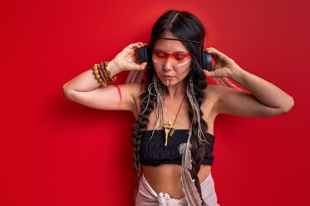 Jovem mulher pagã é uma xamã isolada na parede vermelha