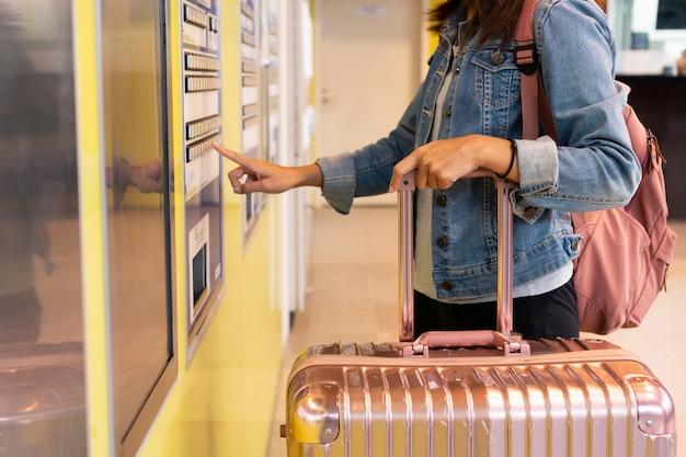 Jovem mulher pagando na máquina de bilhetes em uma estação de trem