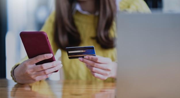 Jovem mulher pagando online por smartphone e cartão de crédito, compras online, banco online.