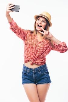 Jovem mulher paquerando feliz tirando fotos de si mesma pelo celular, sobre fundo branco