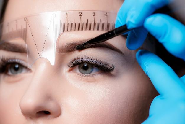 Jovem mulher passando por procedimento de correção de sobrancelha em fundo claro