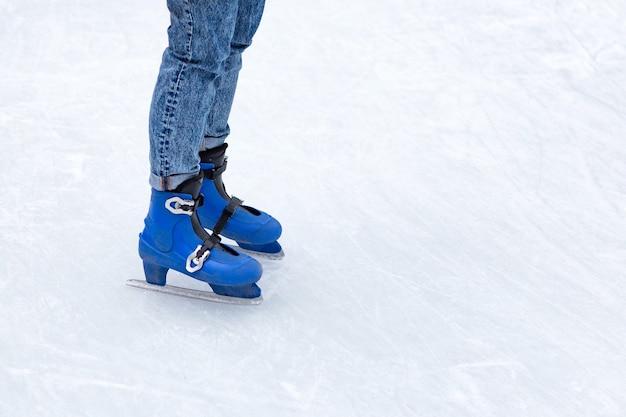 Jovem mulher patinando no lago congelado ou na pista de gelo ao ar livre no inverno nevado.