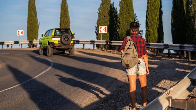 Jovem mulher pedindo carona ao longo da estrada. autostop de viagem de garota. vista traseira