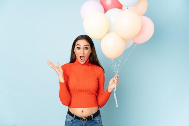 Jovem mulher pegando muitos balões isolados na parede azul com expressão facial de surpresa