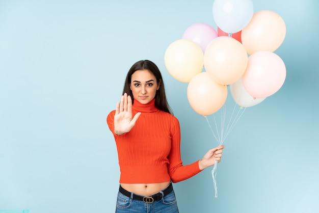 Jovem mulher pegando muitos balões isolados na parede azul, fazendo o gesto de parada com a mão