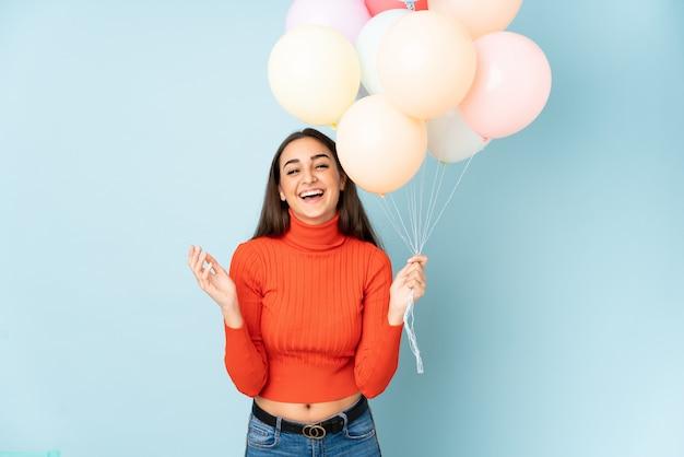 Jovem mulher pegando muitos balões isolados na risada azul