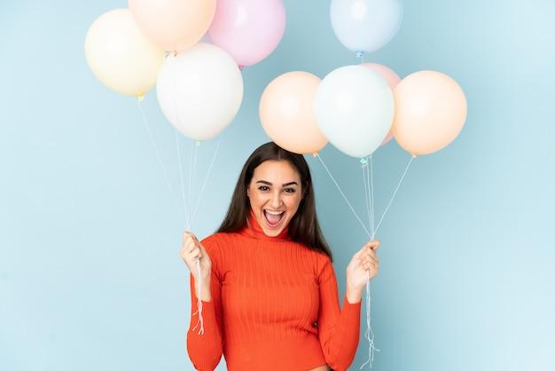 Jovem mulher pegando muitos balões isolados no azul