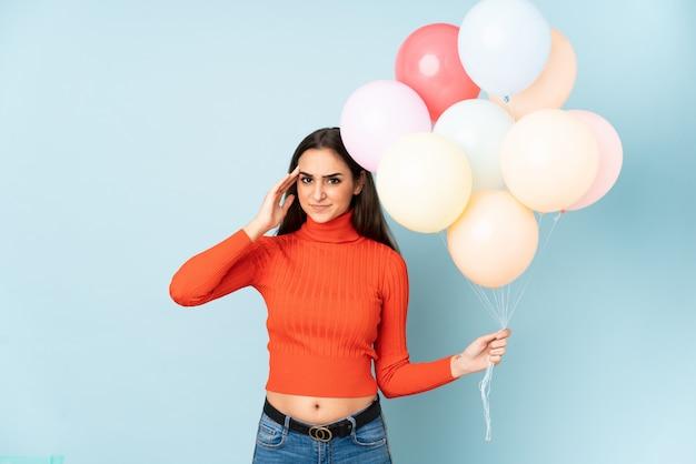 Jovem mulher pegando muitos balões na parede azul infeliz e frustrada com algo.