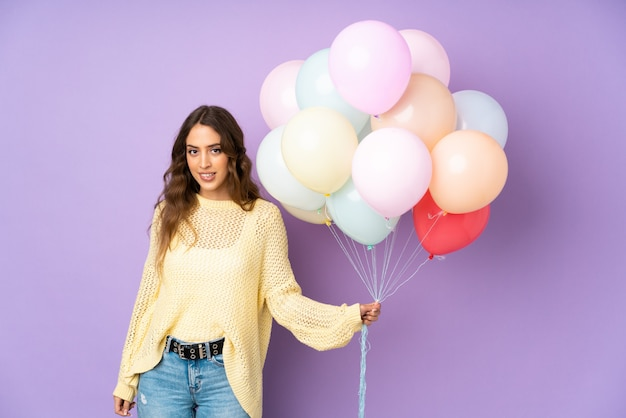 Jovem mulher pegando muitos balões na parede roxa, tendo dúvidas e com expressão de rosto confuso