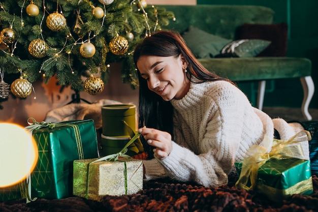 Jovem mulher pela árvore de natal desembalar presentes