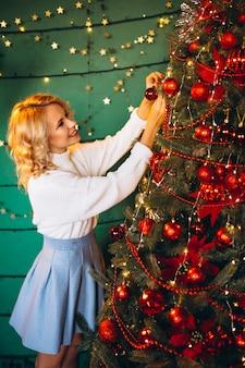 Jovem mulher pela árvore de natal no natal