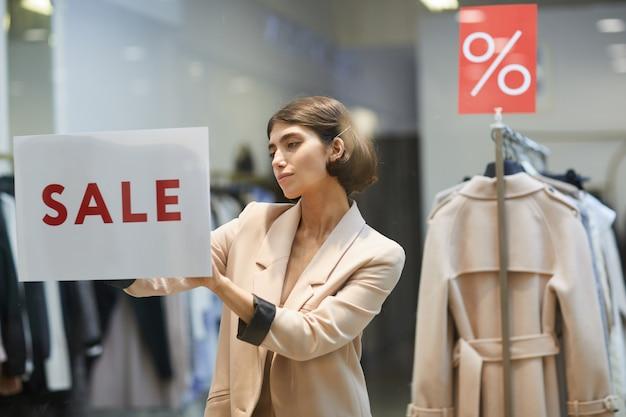 Jovem mulher pendurado sinal de venda na loja