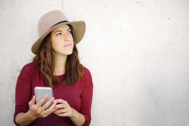 Jovem mulher pensando em responder em seu smartphone