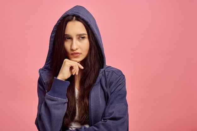Jovem mulher pensativa com capuz, parede rosa, emoção. expressão facial, pessoa do sexo feminino olhando para a câmera no estúdio, conceito emocional, sentimentos
