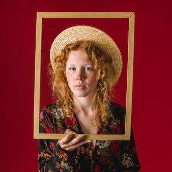 Jovem mulher pensativa do gengibre que guarda o frame de retrato