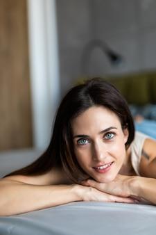 Jovem mulher pensativa feliz que encontra-se e que pensa na cama.