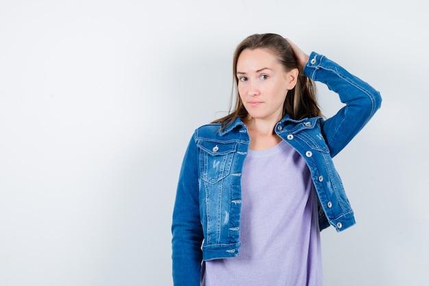 Jovem mulher penteando o cabelo para trás em t-shirt, jaqueta jeans e parecendo sensata, vista frontal.