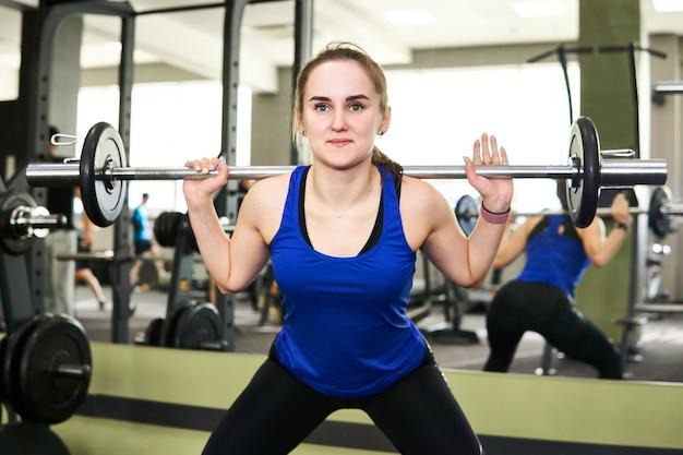 Jovem mulher pequena fazendo exercícios de agachamento com barra na academia refletindo no espelho