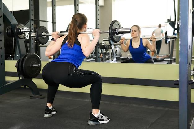 Jovem mulher pequena fazendo exercícios de agachamento com barra na academia se olhando no espelho