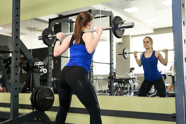 Jovem mulher pequena fazendo exercícios de agachamento com barra na academia