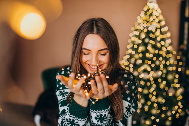 Jovem mulher perto da árvore de natal com luzes brilhantes de natal