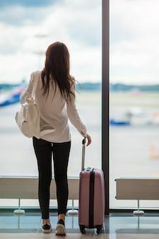 Jovem mulher perto de grande janela panorâmica em um saguão do aeroporto esperando chegar