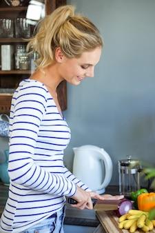 Jovem mulher picar cebola no balcão da cozinha