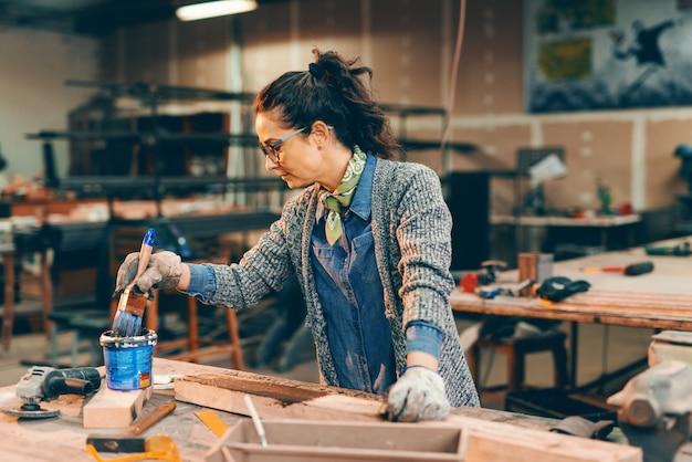 Jovem mulher pintando a prancha de madeira na mesa de carpintaria