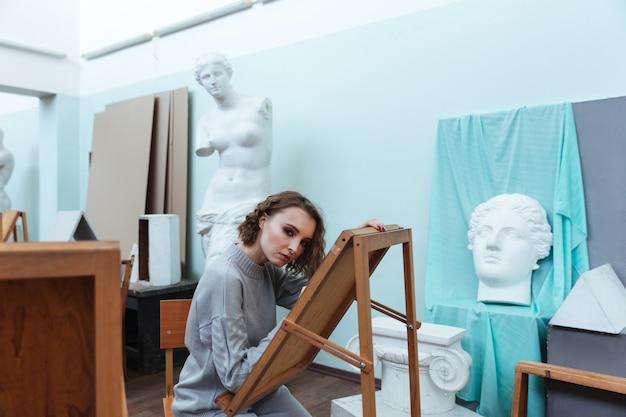 Jovem mulher pintando enquanto está sentado