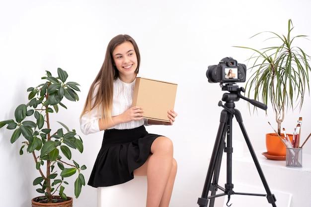 Jovem mulher pintando foto criando conteúdo online em fundo branco com espaço de cópia