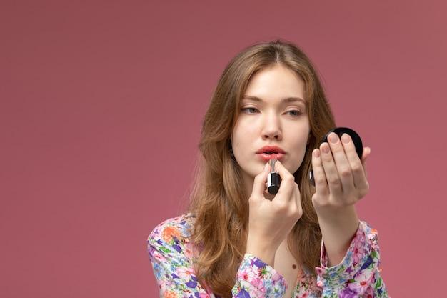 Jovem mulher pintando os lábios com batom e usando um mini espelho