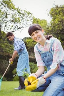 Jovem mulher plantando um rebento no jardim e homem limpando a grama
