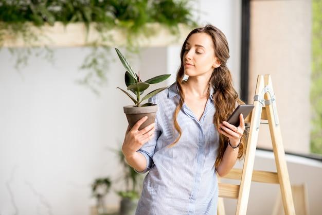 Jovem mulher plantando uma casa com vegetação em pé com o telefone e o vaso de flores na escada