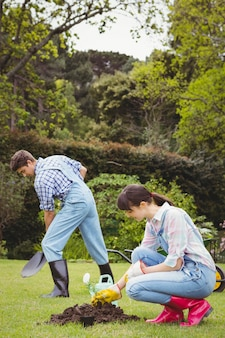Jovem mulher plantando uma muda no jardim