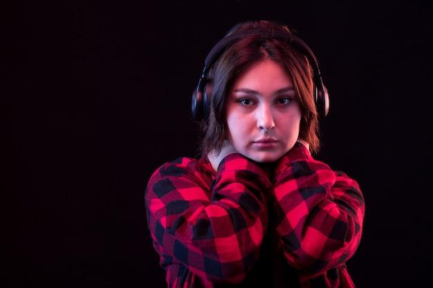 Jovem mulher posando com camisa vermelha e preta quadriculada usando fones de ouvido