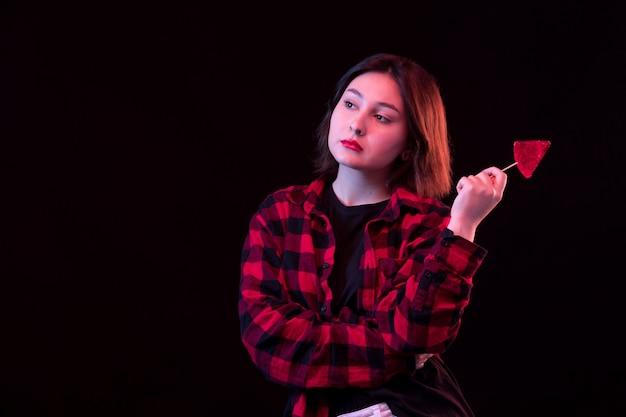 Jovem mulher posando com camisa vermelha e preta quadriculada